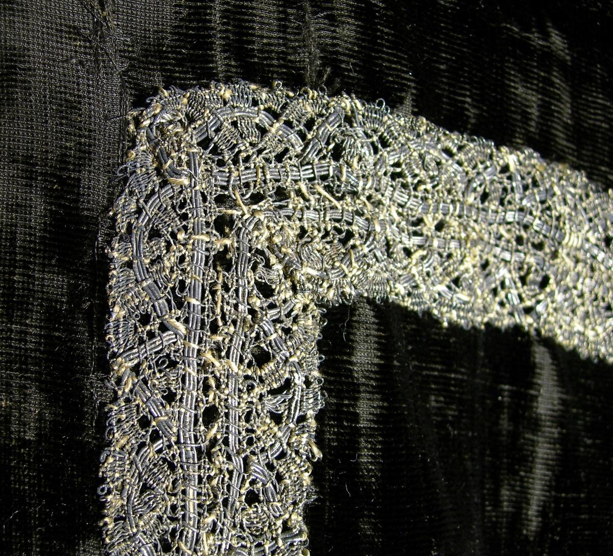 Slät sammet, svart. Varp: svart silke Polvarp: svart silke Inslag: svart silke Yllefoder i liksidig kypert (2/2), gråsvart. Tidigare foder, alternativt mellanlägg, i linne, 3-skaftad kypert (2/1), oblekt. Mässhaken har axelsöm och en del av yttertyget mitt fram är av grövre ylle?sammet. På framsidan 840 x 220 mm U-formad dekor av 2 spetsar i metalltråd (spunnet lan, silver) tillsammans 37 mm. Halsringning samt 110 mm djupt sprund med 15 mm bred spets i metalltråd (spunnet lan, silver).  På baksidan 1070 x 520 mm stort kors med konturer av 2 spetsar i metalltråd (spunnet lan, silver), tillsammans 30 mm breda. IHS/A 1667 applicerat i korset med 5 mm brett tuskaftsband vävt av metalltråd (spunnet lan, silver).
