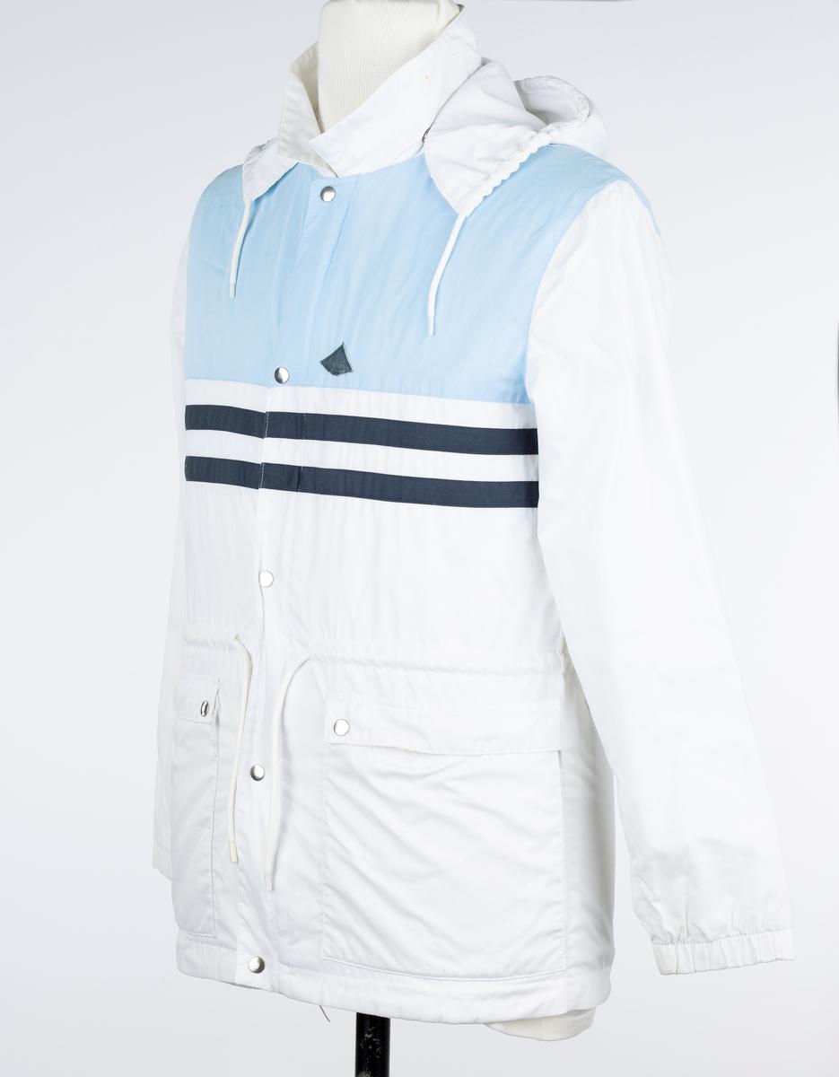 Jakke med hette. A: Jakke. B: Hette. A: Hvit jakke. Glatt blandingsstoff.  Lukkes med plast glidelås og i isblått stoff.  5 trykknapper. Løpegang med snøring i livet. Lomme med klaff på hvert sorstykke. Øverste del av front og rygg i isblått stoff. 2 mørk blå striper både på utside og innside.  Kjøpt ca 1982. Brukt på jobb i Dysterlia Banehage i Ås til 1983