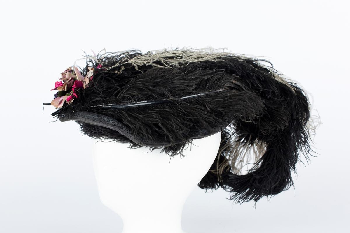 """Hatt. Damehatt med sorte og noen lysestrutsefjær. Hatten har et ovalt utseende.  Lett bøyleformet hattebunn i sort stivet linstoff: Rett side, over denne hattepull med brem kantet med ståltråd. Hattepullen dekket med strutsefjær. Foran festet en bukett silkeblomster i rød-violette farger, grønne stilker og blad.  Giver Olga Ambjørnrud:  """"Hatten tilhørte mor, Olea Bolette Ambjørnrud, 1862-1926. Hun brukte den når hun skulle være fin. Hun hadde da alltid på seg silkebluse med masse sømmer og nål i kragen, fint skjørt og fin kåpe. Mor brukte alltid svart""""."""