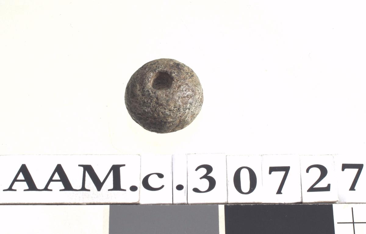 Lite spinnehjul av kleberstein, av type som Vikingetidens Redskaper, fig. 164, men noe mindre. - Tverrmål 3 cm.