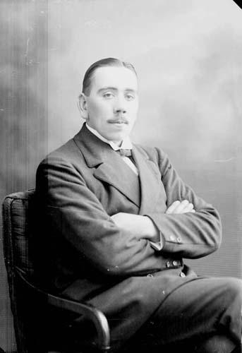 Porträtt av en man med mustasch som sitter i en fåtölj med armarna i kors.