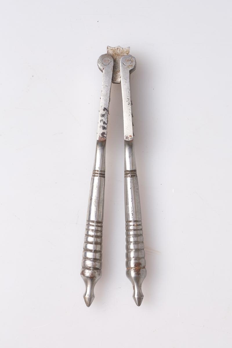 Nøtteknekker av stål bestående av to armer som er hengslet i den ene enden. Nederst på hver arm er det dekorert med profiler av åtte ringer. På knekkeflaten er små hull på hver side.