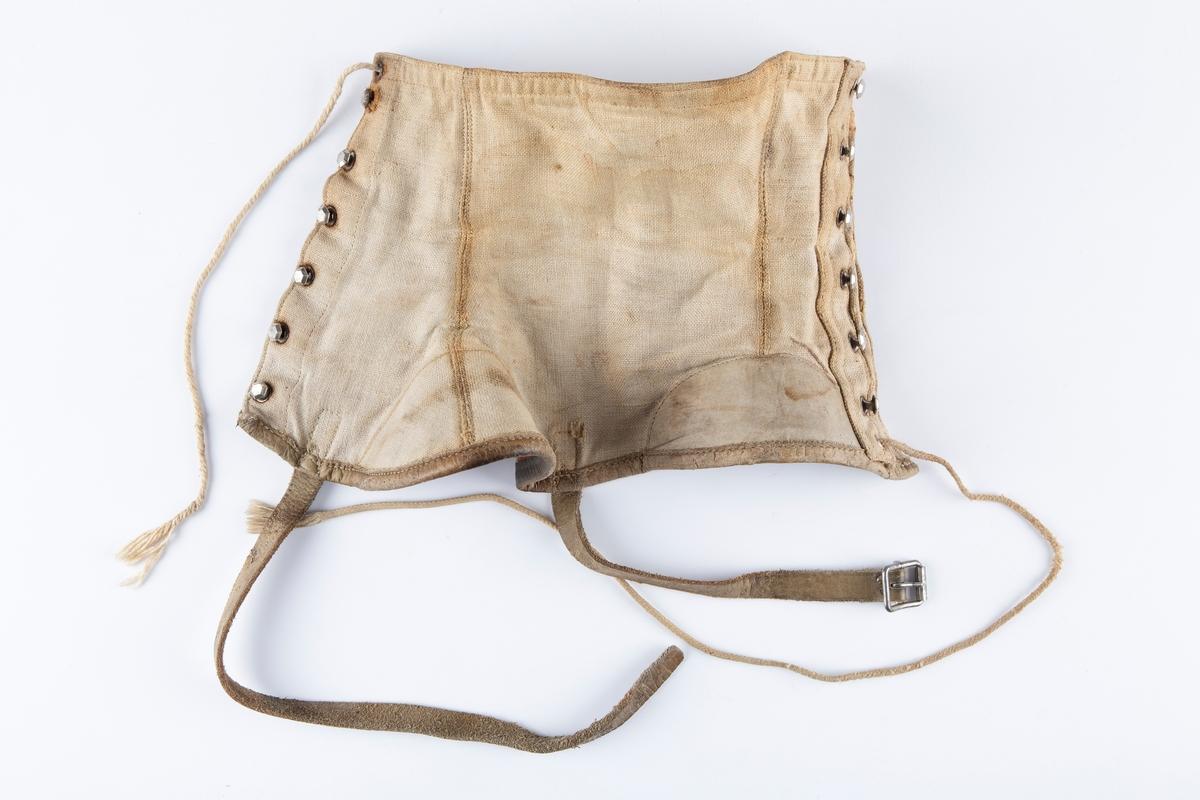 Fasongsydde gamasjer, ett par, lukkes på ytterside med snøremaljer. Forsterkede kanter og sømmer. Nedre kant har skinnkant. Lærstropp til fastspenning under skistøvel.