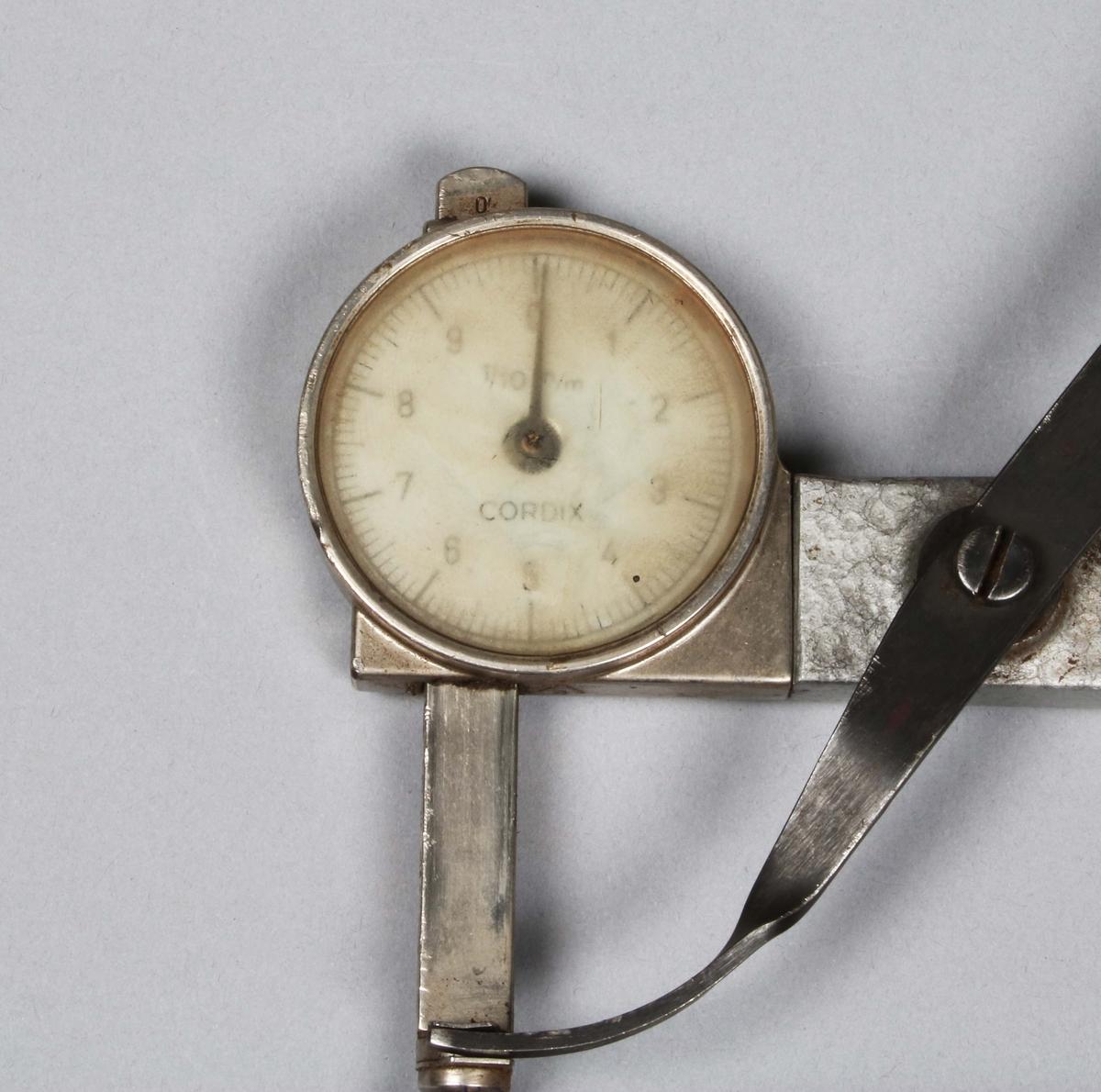 Mätinstrument i grå lättmetall med rund siffertavla, graderad 1-9. Under glaset märkt: CORDIX 1/10 m/m. Användes för att mäta tjocklek på olika läderkvaliteter för skotillverkning. Proveniens Wiskania Sko AB, Borås.  Historik:  N.H Ljungberg startade år 1903 en läderaffär på Allégatan i Borås och företaget utvidgades och kom även omfatta partiförsäljning av skodon och galoscher. År 1916 startade Ljungberg läderfabriken vid Gässlösavägen. Fabrikens produktion bestod till en början huvudsakligen av bottenläder men utökades senare till att även innefatta diverse ovanläder och sulläder. Under 1940-talet bildades ett antal dotterbolag till företaget för tillverkning av skor och tofflor. Vid den här tiden fanns det 75 anställda vid fabriken i Borås. Samtliga bolag som var knutna till fabriken samlades senare under företagsnamnet Wiskaniabolagen. År 1969 ingick AB Ljungbergs läderfabrik, AB Ljungbergia, Sko AB Wiskania samt försäljningsbolaget Wiskania AB i bolaget. År 1972 blev Wiskania Sko AB löntagarägt, av drygt 100 anställda gick 92 personer in och blev delägare i bolaget. Verksamheten vid Wiskania Sko AB lades ner under 1991.  En storsäljare ända in i nutid, var skor i allmogestil till folkdans och dylikt.