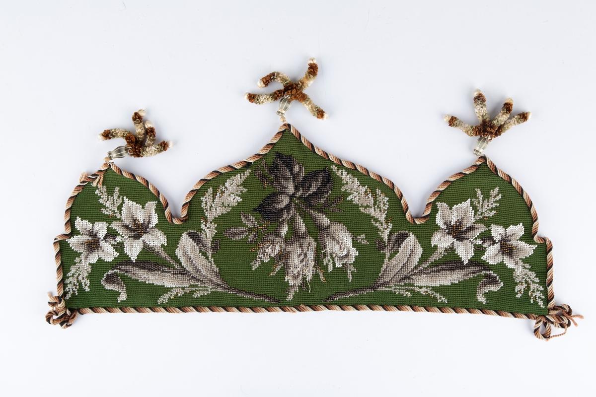 Rektangulært perlebroderi med tre tunger, dusk på hver tunge.  Grønn korsstingsbunn. Perlebrodert blomster (ligner liljer) og blad. Til å henge på pipestativ. Har tilhørt Thale og Ragnhild Hoelstad d.e (født Hvitsten).