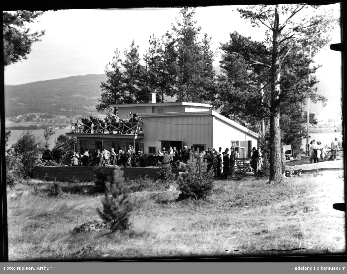 Skytterstevne. Mange mennesker samlet ute foran skytterhuset på Frydenlund skytterbane, Jevnaker.