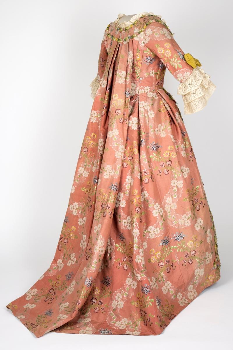 Overkjole av silkebrokade med tilhørende skjørt av samme materiale, begge prydet med blomsterranker av possement. Watteau-folder. Se undernummer.