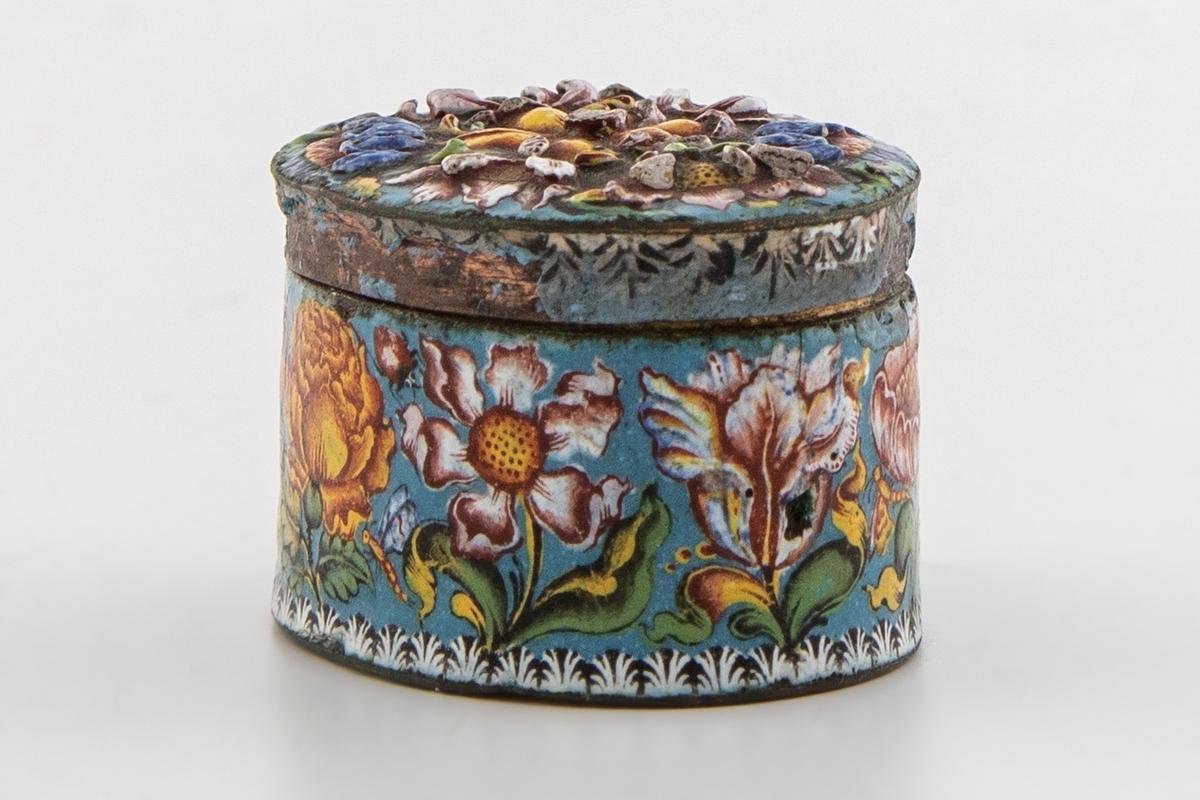 Liten flat, oval eske, metall med blå opak emalje og polykrom detaljert blomsterdekor på eskens utside og lokk. Små insekter er avbildet blandt blomstene. På lokket er blomsterdekoren uthevet i relieff og danner et symmetrisk mønster. Lite hvit, dekorativt bladmønster rundt lokkets kant og nedre kant på eskens utside. Innsiden av esken er blå, mens undersiden er forgylt.