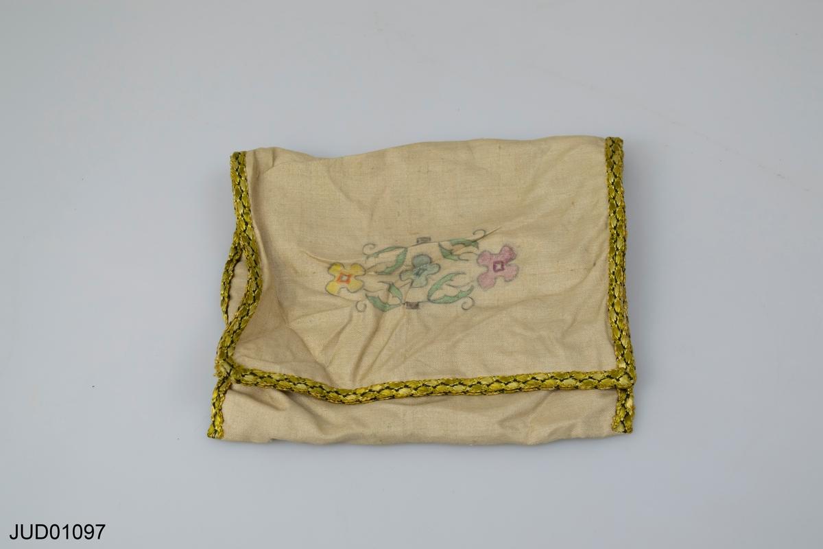 Påse i vitt siden med guldbård. Har två fakc inuti och målade blommor på framsidan.