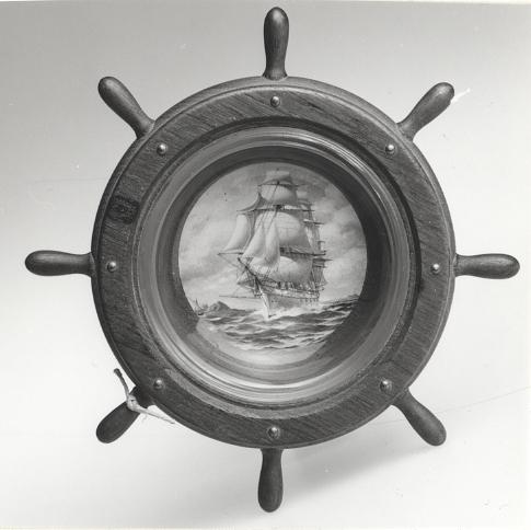 Av teak från korvetten FREJA. Infäld glasskål med bild på FREJA. Färgtryck målad efter J Häggs original