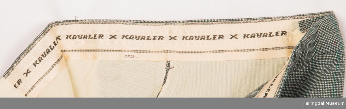 Kavaler herredress, jakke og bukse i grønt spettede tøy. Grønt syntetisk silkefor. Jakka har skulderputer, klaff på lommene, 1 splitt bak og store slag på kragen.  Den er knept med 2 knapper midt framme.  3 pynteknapper på hvert erme. Buksa har sleng.