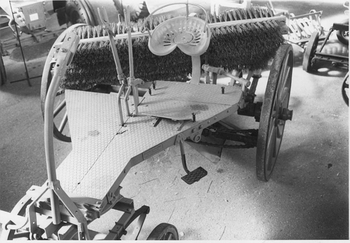 Gråmålad sopmaskin. Hästdragen, chassi med två stora trähjul med ekrar, rödmålade. Roterande borste baktill, delvis bevarad. Sittplats (typ hästräfsa), två spakar för reglering av borstarna. Anordning för koppling till hästskaklar.
