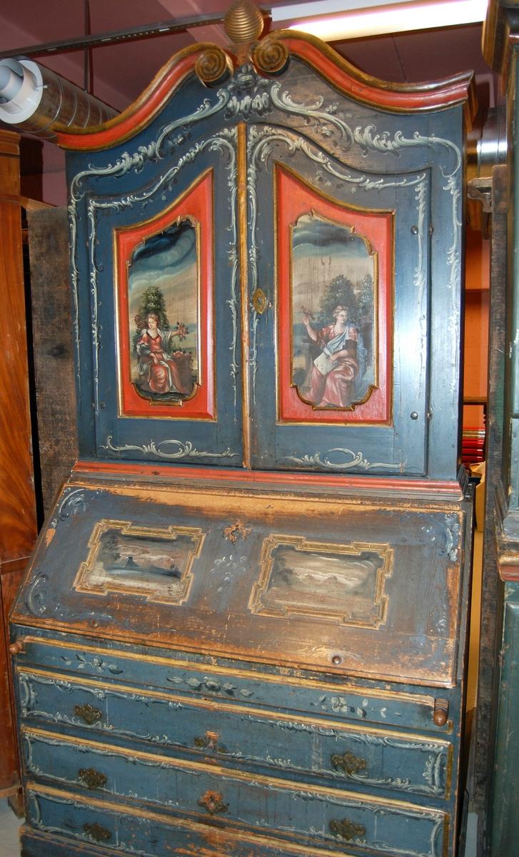 Skatoll av tre. Skapet har blå grunnfarge, og hvit og mørkeblå barokkmaling. På nederste del er det tre skuffer, med parvise håndtak laget av kobberlegering med gjennombrutt dekor. På øverste del av skapet er det to skapdører med fyllinger. I fyllingene er det malt dekor med motiv av to mennesker med blomster og fugl i hendene. Skapet har konveks koll, med to lister med gullbelagte kanter som ender i to volutter på midten. Mellom voluttene er det en gullbelagt kule med dekorative tverrsnitt. På den nedfellbare platen er det to fyllinger med profilerte lister, og malt dekor av landskapsmotiv.