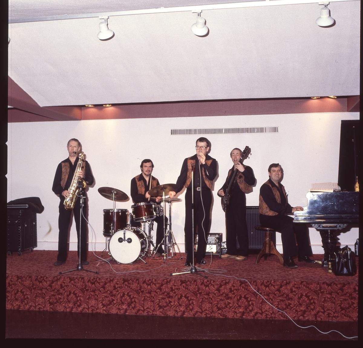 En positiv filmremsa på fyra bilder av ett dansband som spelar på en scen.