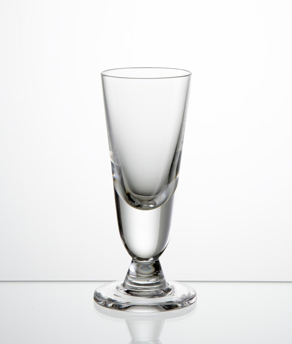 Brännvinsglas med lätt konande form med kort ben på fot.