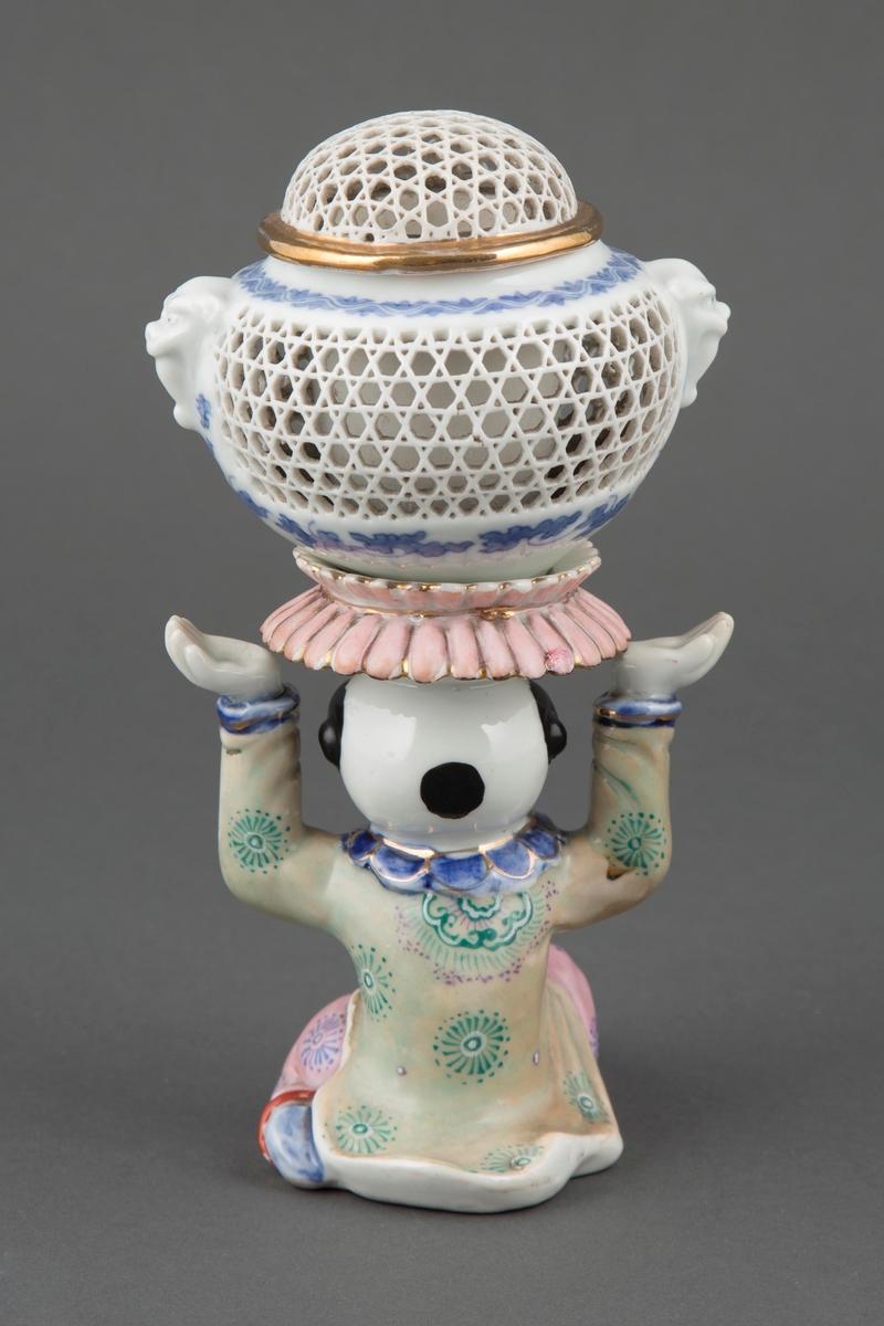Røkelseskar i glasert porselen, utformet som en statuett bemalt med over- og underglasurmaling. Holderen er utformet som en knelende kineserer, iført en grønnfarget changsan samt rosa bukse. Begge delene er dekorert med rosetter, henholdsvis i mørk grønn og blå. Figurinen bærer et røkelseskar med hvelvet lokk, hvor den gjennombrutte overflaten består av stjerneformer. Karet er dekorert med to dyremasker samt stilisert plantedekor i blå underglasurmaling. Forgylt detaljering.