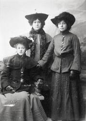Gruppeportrett av tre  ukjente damer med hatt og kåpe, visit