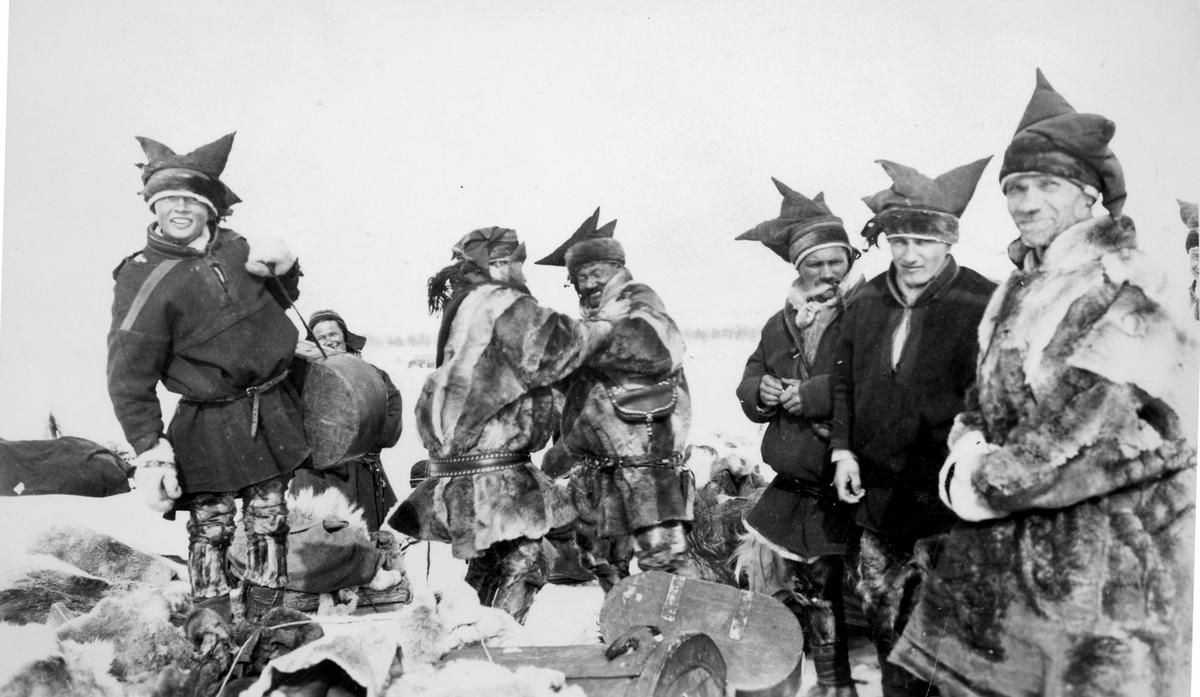 Gruppebilde av samiske gutter og menn, tatt utendørs om vinteren.