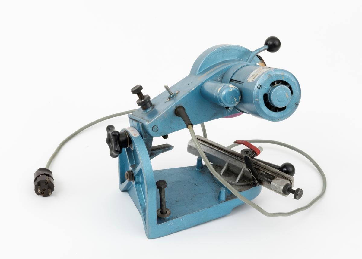 Elektrisk slipemaskin, smergelskive, benkslipemaskin, med en skive brukt til sliping av kjeder til motorsager og hogtsmaskinaggregater ved skogskolen på Sønsterud i Åsnes kommune. For registrator ser det ut til at slipemaskinens komponenter hovedsakelig er utført i presstøpt metall.    Slipemaskienen består av tre hovedkomponeneter: en ramme (brakett, sokkel), motorhus med slipeskive og holder for sagkjede. Braketten, som består av en fot (sokkel) og en del som er vertikalt montert til foten (sokkelen). I sokkelen er det to gjennomgående skruer som gjør det mulig å feste maskienen til en arbeidsbenk. Holderen for kjedet og motoren som driver slipeskiva er begge festet til braketten (ramma). Kjedeholderen er festet til foten (sokkelen), mens motoren som driver slipeskiva er montert til den vertikale delen av braketten.  I bakkant av den vertikale delen av ramma, er det en reguleringsskrue med ratt i hardplast. Ved å løsne denne skruen, kan motordelen beveges i en slisse. Her er det satt opp en skala med gradtall 40 til 90, som angir slipeskivas hellingsvinkel mot kjedet. Kjedeholderen lengst fram på foten (sokkelen) kan også vinkles fra -40 til +40 grader. En skrue med et ratt av hardplast som er plassert på undersiden av sokkelen kan løsens og slik kan kjedeholderens vinkel justeres. Foran kjedeholderen er det et håndtak som benyttets når kjedet skal klemmes fast og løsnes fra kjedeholderen. På motordelen gjenfinnes et håndtak med en kule av hardplast. Håndtaket brukes når slipeskiva skal presses ned mot kjedet. Det er også en stoppeskrue på motordelen som gjør at slipeskiva holder samme avstand til sagkjedet under hele slipeprosessen. Skruen er gjennomgående og  den støter an mot en metalldel på undersiden når slipeskiva presses ned mot kjedet. Skruen kan stilles inn på ulike nivåer. Like ved denne skruen gjenfinnes også en av-og-på-knapp  i blankt metall.