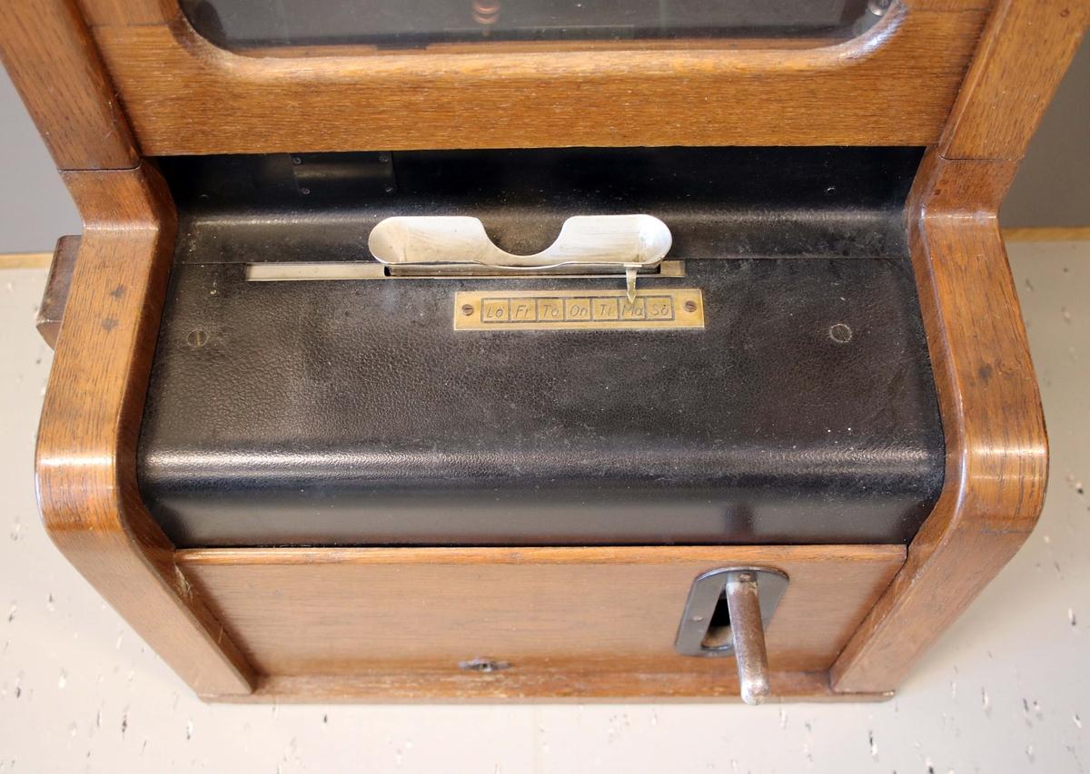 """Stämpelur, stämpelklocka. Elektriskt. Rektangulärt, brunbetsat ekfodral, med lås och öppningsbar, glasförsedd dörr. Upptill, monterad vit urtavla med svarta arabiska siffror. Uret, med hängande lång ekpendel och kopparfärgat, runt, konvext lod. Nedtill, utskjuten låda, med rakt utstående handtag på höger sida. Ovanför, avlångt hål för att stoppa in stämpelkorten. Framför hålet mässingsbricka märkt: Lö Fr To On Ti Må Sö. På krönet, kopplingsdosa. Baktill, järnbeslag för upphängning. Proveniens Marks Pelle Vävare, Kinnahult.  """"Detta stämpelur styrdes av ett centralur. Se centralur BM 80409, som användes på Marks Pelle Vävare AB i Kinnahult, fram till 1989. Genom att skicka en strömsignal på 24 volt, i några sekunder, med antingen 30 sekunder eller en minuts intervall, beroende på fabrikat. Detta görs, med ett mekaniskt relä, styrt av centraluret. I övriga ur, finns en spole som skapar ett magnetfält vid varje signal, som i sin tur, drar fram urverket och visarna. På så vis, hade man alltid exakt samma tid, i hela fabriken och behövde bara ha koll, på att ett ur hade rätt tid"""".  (Ett stämpelur eller en stämpelklocka är ett ur som används för att registrera när anställda anländer till och avviker från arbetsplatser. Stämpelklockor var tidigare mekaniska men är numera helt elektroniska. Med elektronikens hjälp har man numera tagit fram stämpelur som kan räkna, d.v.s. de summerar varje dag och hela perioden) Wikipedia  Historik: Donatorn arbetade på Marks Pelle Vävare i Kinnahult till sin pensionering 1997. De sista åren arbetade han i  varpsalen, där han skötte konvarpan. Han bodde hela sitt liv på familjens föräldrahem i Örby, som han köpte efter moderns död. Även den äldre brodern bodde kvar på samma adress.  Donatorns teknikintresse var stort och han skötte om familjens gamla väggur med stor entusiasm, det föll sig därför ganska naturligt i slutet på 1980-talet, när man ersatte de gamla fabriksuren på Marks Pelle Vävare med ett digitalt system, att han tog hand om des"""