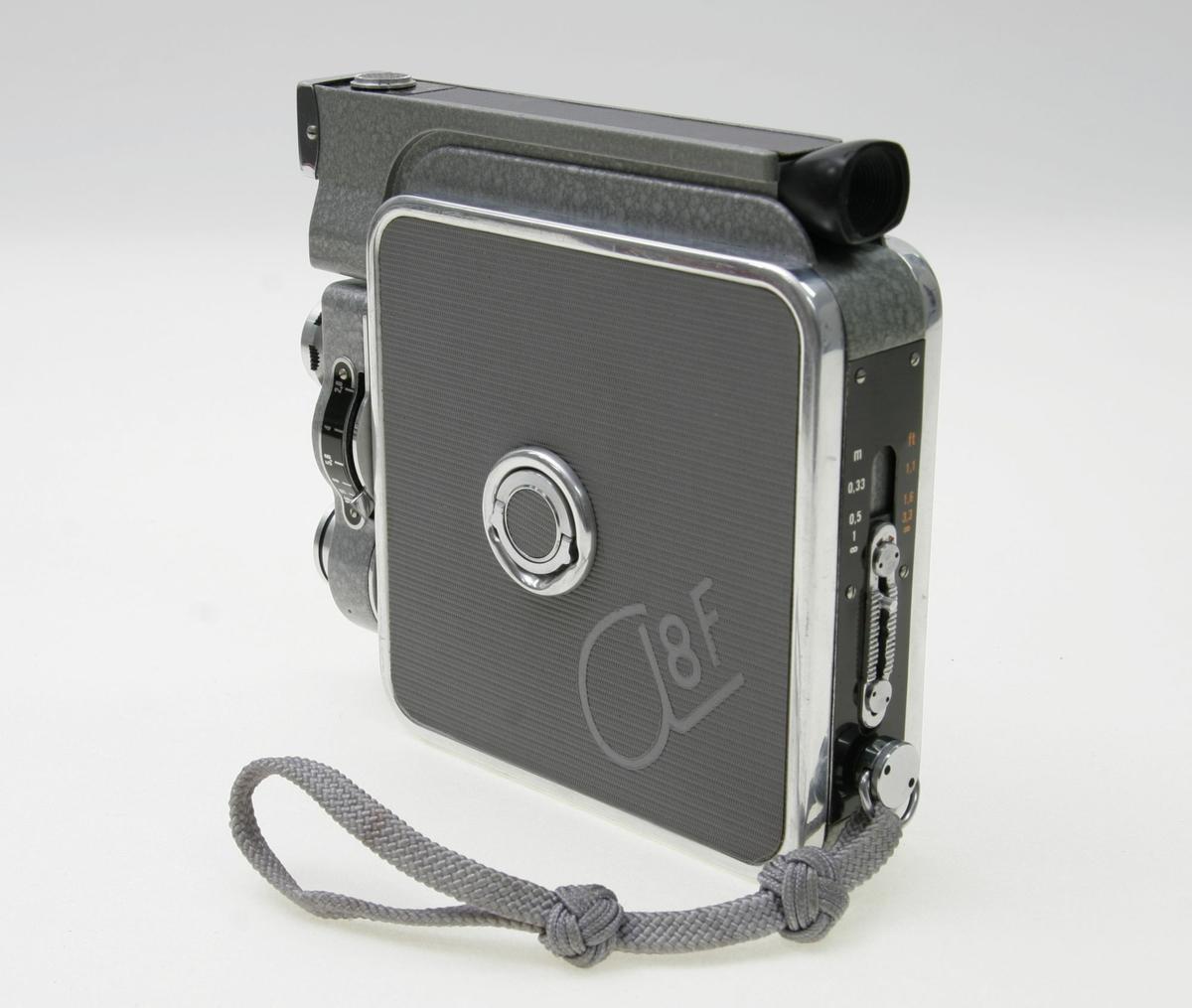 Filmamera I original lærveske med skulderreim med handtak for kameraet. Brennvidde 12,5mm. Blender 2,8 - 16 (linse). Innebygd lysmåler. Justerbar søker. 16 bilder i sekundet. Instillinger for ASA (lysfølsomhet). Zoom 0 - 7,5m. Handtak på sida for å spole filmen. Liten vridbar knapp på andre sida av kameraet for å åpne inn til fimen.