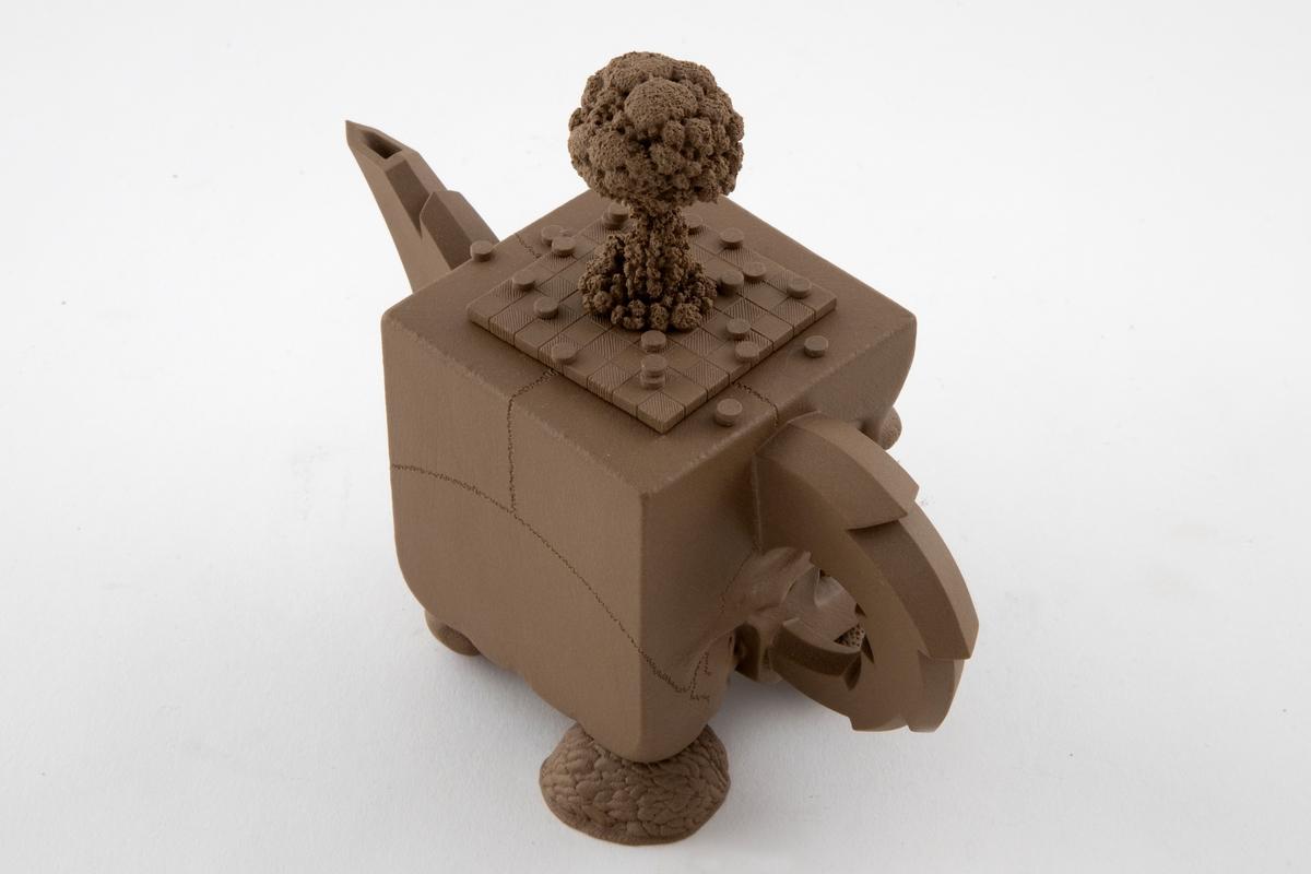 Tepotte i lys, brunfarget keramikk. Korpus er firkantet og formet som en hodeskalle. Helletut og hank er taggete og formet som lyn. Korpus står på fire føtter formet som skallene til peanøtt, mandel, hasselnøtt og valnøtt (halv). Lokket er løst og ser ut som et Dam-spillbrett med brikker fordelt på og utenfor brettet. Lokknappen er formet som er soppformet røyksky som stiger opp fra spillbrettet.