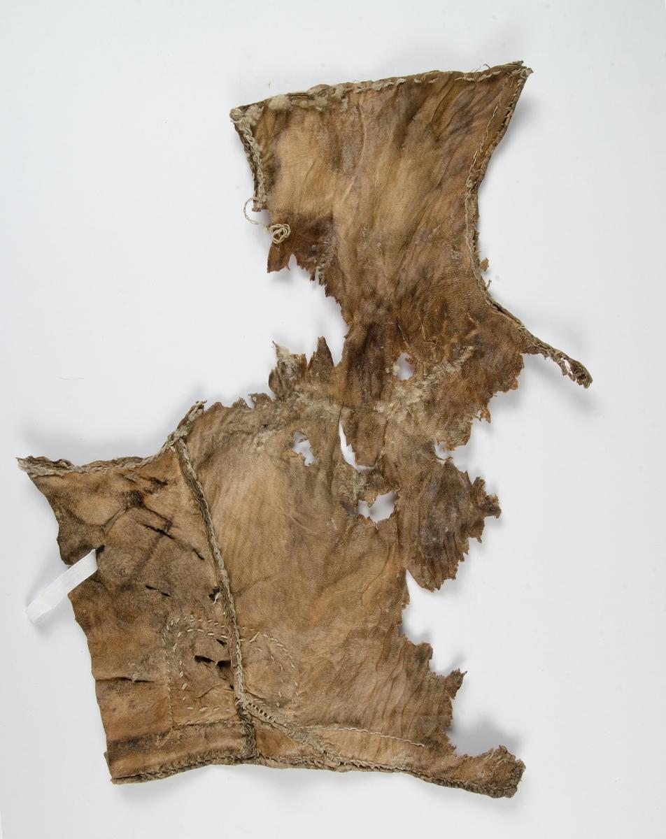 Fragment av pälsplagg. Minimala pälsrester på insidan. Troligen framstycke på kvinnotröja med halsringning, ärmringning och slå i nederkant. Dekorativ kant med skinn med uddkant (zick zack mönster) runt halsringningen.