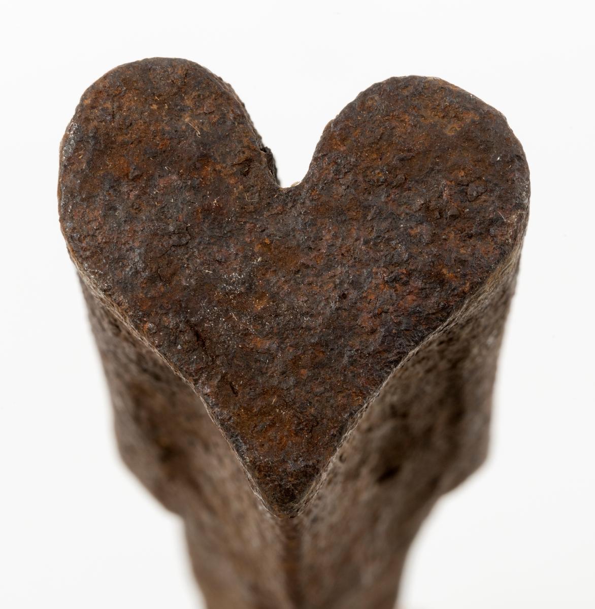 Stempelmal, brukt til å forme de profilerte eggpartiene på blinke- og merkeøkser. Redskapet er 34,5 centimeter langt hvorav den profilerte delen utgjør cirka 8 centimeter av lengdemålet. Denne delen er en aning kon – tjukkelsen tiltar noe fra ytterenden og innover. I ytterenden er tverrmålet 3,1 X 2,0 centimeter, innerst 3,7 X 2,4 centimeter. Profilen på stempelmalen er hjerteformet. Dette symbolet er verken funnet på Christiania Tømmerdirektions merkekart fra 1900 eller på Glomma fellesfløtingsforenings merkekart fra 1960. Skaftet har et noenlunde kvadratisk tverrsnitt, men med noe avfasete kanter. Det smalner litt mot den bakre enden, som er noe stuket etter hammerslag under øksesmiinga. Den fremre delen av skaftet og merkedelen er buet. Gjenstanden veier 1 250 gram.