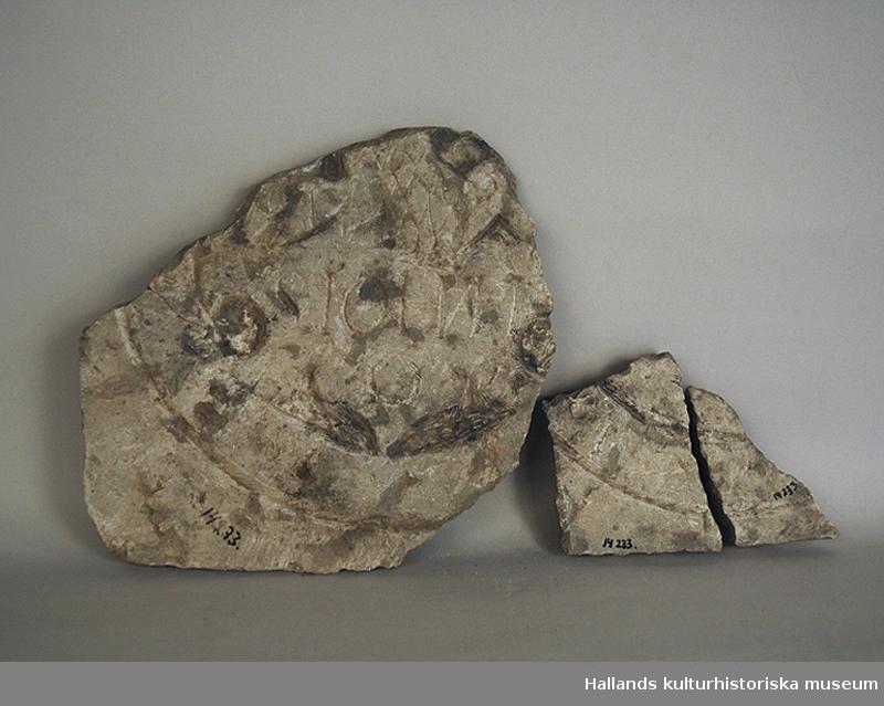 Gravsten, tre delar. Mått: a) längd 12 cm, bredd 10 cm, tjocklek 2,5 cm. b) längd 26,5 cm, bredd 25,5 cm, tjocklek 3 cm. c) längd 13 cm, bredd 6,7 cm, tjocklek 2 cm.