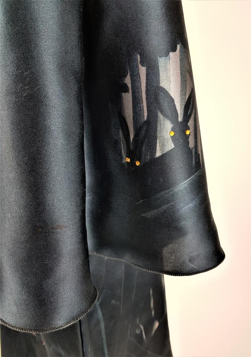 """Kjole i silke med print av skogmotiv på nattestid, med skogsdyr og fugler. Dyrene har pålimte Swarovskikrystaller av ulik farge som øyne. Kjolen er relativt kort og har et tilnærmet primærsnitt, med rett isydde ermer, løpegang med strikk i livet og et smalt knyttebelte. Den har """"nedsenkede"""" skuldre, vide, albuelange ermer, samt båtringning."""