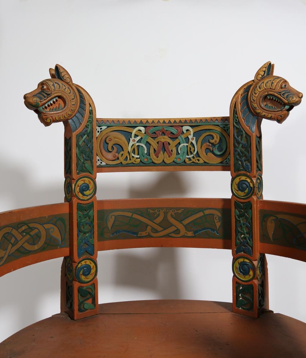 Stol. Sete i form av en halvsirkel, med to stolben i front og to ved bakre del. De to bakre stolben fortsetter opp fra setet og utgjør stolryggen, der de ender med to utskårede dyrehoder i topp. Tre buede trestykker er plassert mellom de vertikale stolpene og utgjør ryggstøet og armlener. Stolen har også en ekstra plate i ryggen, plassert litt høyere. En lignende plate binder også de to stolbena i front sammen. Disse to platene har utskjæringer inspirert av norrøne motiver med ormelignende skapniner som slynger seg rundt hverandre i mønster. Den nedre platen har også utskjæring av en mann med sverd som kjemper mot en drage. Skal antageligvis avbilde Sigurd Fåvnesbane.  Stolbena har også dekorative utskjæringer i lignende stil. De to i front er kronet med to stiliserte ansikter og en kvadratisk topp. Stolen er malt lys brun og alle utskjæringene er malt i forskjellige farger.
