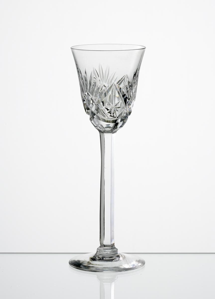 Brännvinsglas, svagt klockformad kupa med skärslipad dekor. Högt fasettslipat ben med slät fot.