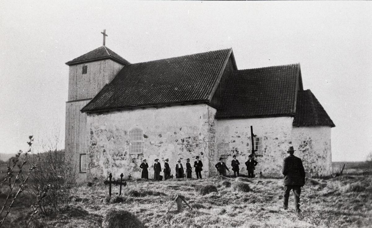 Romnes kyrkje i Nome kommune med personar framfor