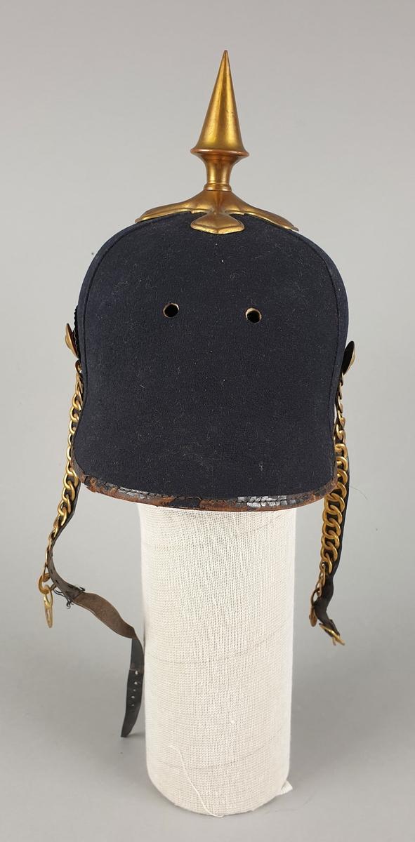 Svart hjelm av semsket skinn med pigg av gullfarget messing. Kokarde av messing i rødt, hvit og blått mellom hjelm og hakerem. Hakeremmer av messing. To hull midt foran.