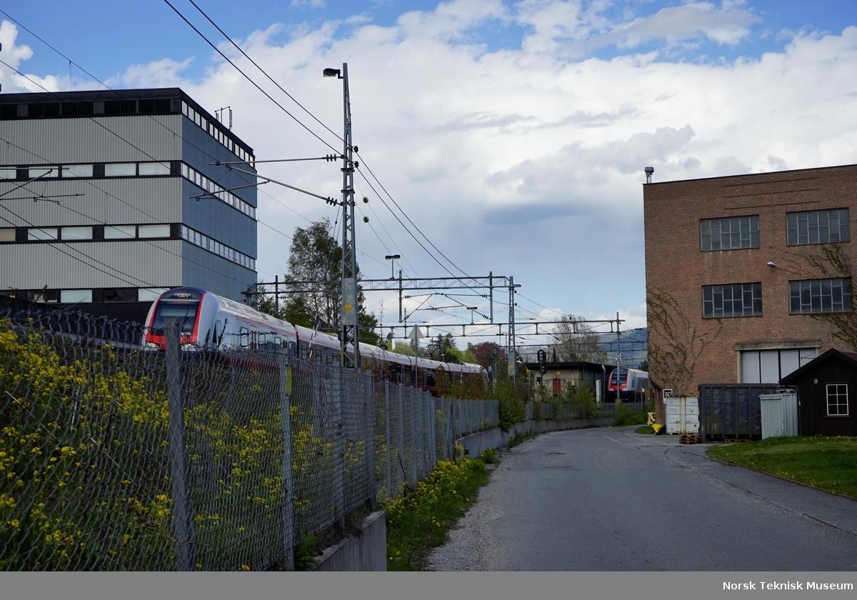 Lokaltog på vei inn på Brakerøya stasjon. Veien hele veien rundt industriområdet på Brakerøya er Jacob Borchs Gate, her mellom hall 41/42 / hall 1 og Drammensbanen, med tidligere Osram-fabrikken på den andre siden. Jacob Borch (1813-1886) var kjøpmann, trelasthandler, industrigründer og kjøpmann fra Drammen.