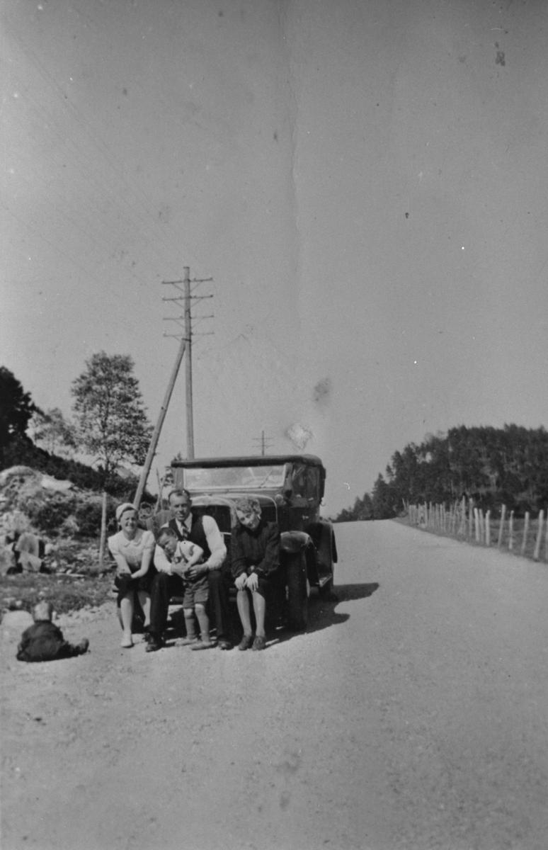 På tur ved Fikse i Ølen, ca. 1940. Bilen er ein Chevrolet 1931. Frå venstre: Anne Haugland, Jørgen H. Haugland, Harald Haugland (på fanget til Jørgen) og Marie Aarro.