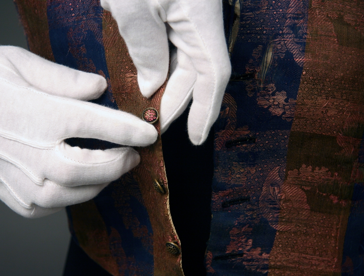 Mansväst av siden och bomullsbrokadtyg med rutig botten i blått och brunt med blomstermönster i rosa. Ryggstycke av brunt och blått rutat bomullstyg. Framstycket är fodrat med linnekypert. Metallknappar och liten krage.