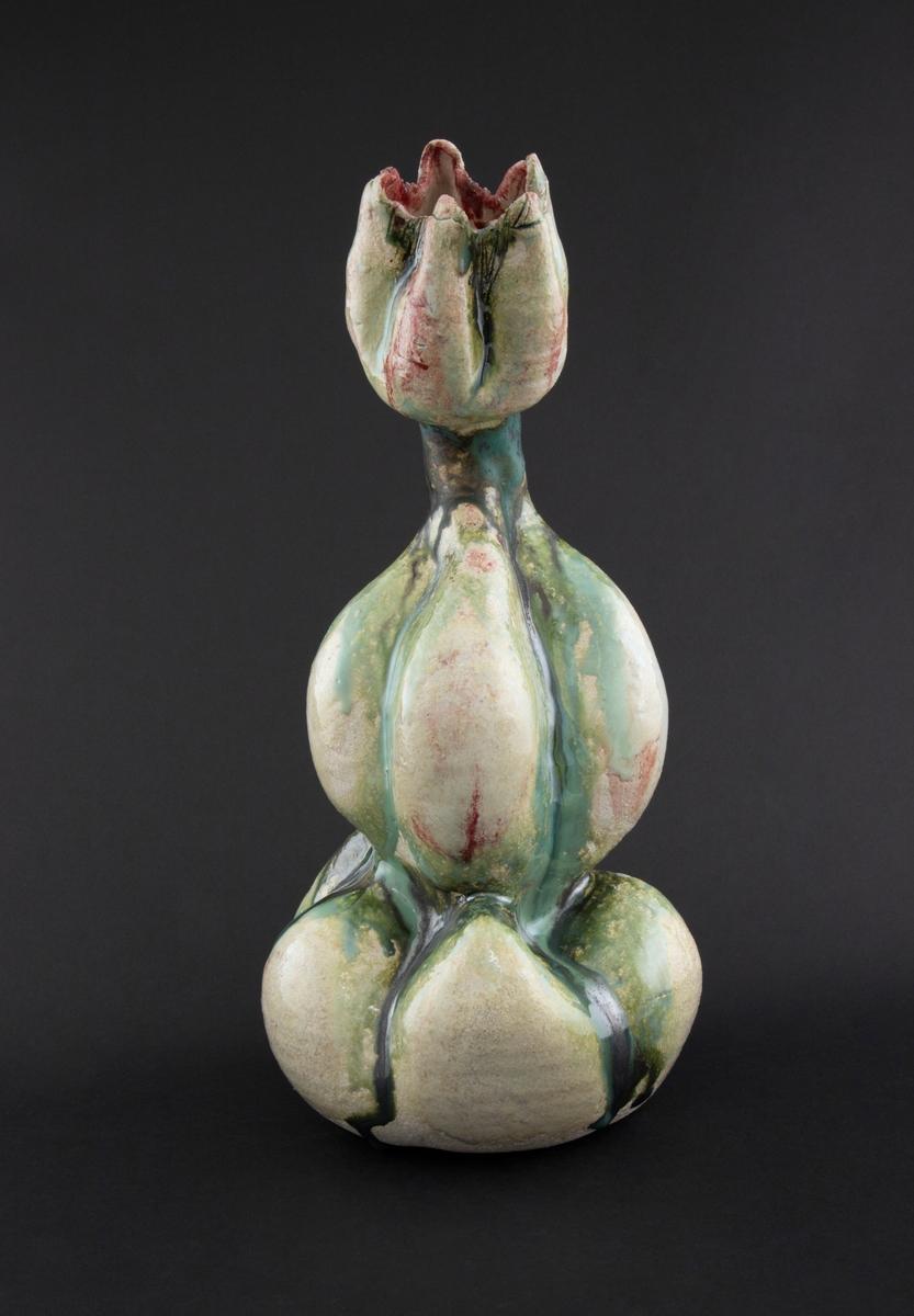 Håndmodellert skulptur i glasert steingods med oppreist holdning. Den har en organisk og asymmetrisk kalebassform som ender i en tulipanform med halvåpne kronblader. Keramikkskulpturen inngår i en installasjon bestående av 26 deler i ulike størrelser og med individuell utforming. De asymmetriske variasjonene gir et inntrykk av bevegelse, og den lett sykelige fargepaletten gir et uhyggelig og grotesk preg. Samtlige deler minner om kjøttetende planter.