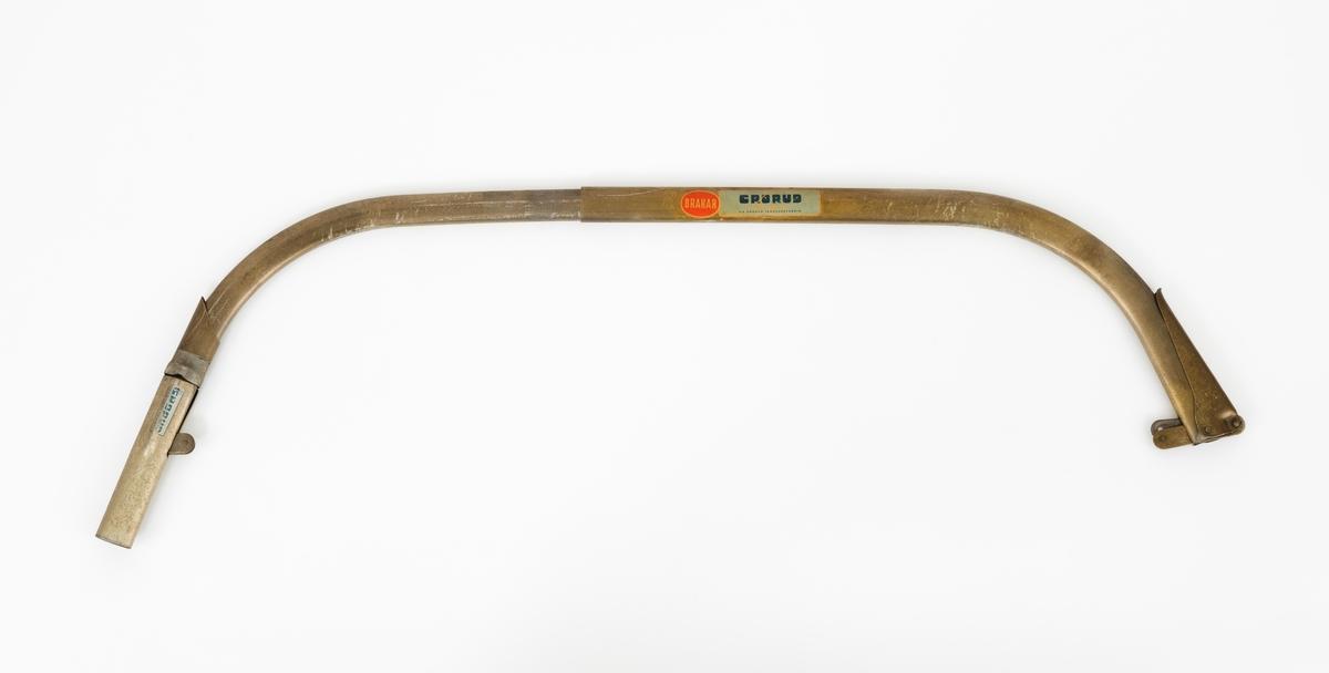 """Gjenstanden består av en rektangulær tretavle med to buesager (bogesager), sagbuer (sagboger) uten sagblad. Montasjen er brukt som produktpresentasjon av Grorud Jernvarefabrikks buesager (bogesager). Dette skjemaet omhandler den ene buesaga (bogesaga), sagbuen (sagbogen). Sagbuen (sagbogen) fra Grorud Jernvarefabrik med betegnelsen """"BRAKAR"""", er utført i ovale stålrør. Det ene rørert er tredd i det andre. Dermed er det mulig å stille saga inn etter ulike bladlengder og dessuten ta den fra hverandre under transport (se s.16 i boka """"Håndbok for huggere"""", 1953). Utfra Jo-Bus Salgskatalog er sagbuen """"BRAKAR"""" stillbar slik at den den kan tilpasses bladlengder fra 36 til 42 tommer. I det ene endestykket, det ene festepunktet for bladet, er det montert en hendel, strammeinnreting for bladet."""