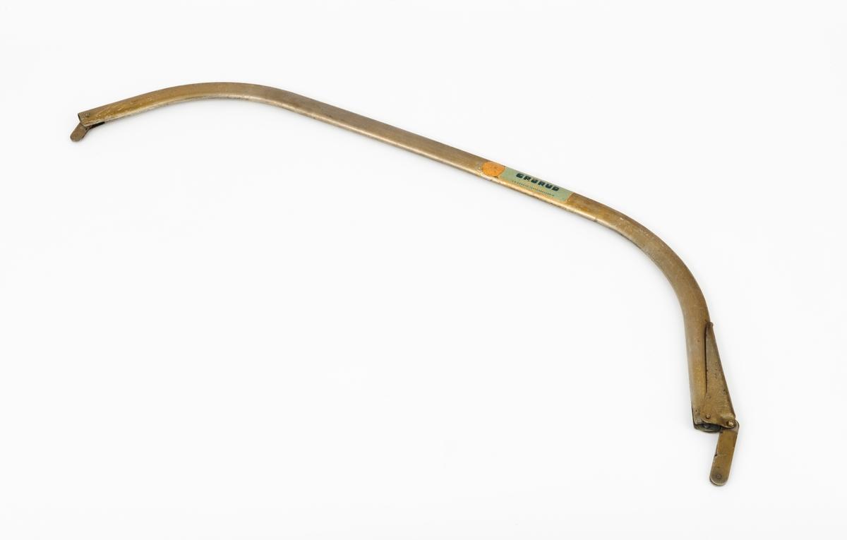 """Gjenstanden består av en rektangulær tretavle med to buesager (bogesager), sagbuer (sagboger) uten sagblad. Montasjen er brukt som produktpresentasjon av Grorud Jernvarefabrikks buesager (bogesager). Dette skjemaet omhandler den ene buesaga (bogesaga), sagbuen (sagbogen). Sagbuen (sagbogen) fra Grorud Jernvarefabrik med betegnelsen """"B"""", er laget av ovale stålrør. Sagbuen (sagbogen) kan ut fra Jo-Bus salgskatalog tilpasses sagblad med disse lengdene: 24"""", 30"""" og 36"""".  I det ene festepunktet for bladet, er det montert en hendel, strammeinnreting for bladet."""