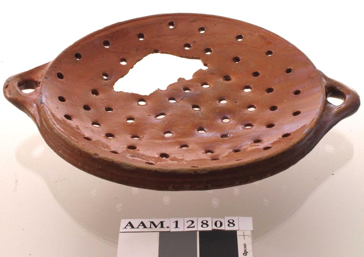 Fiskefat med silehull,  Leirtøy i rødbrunt gods, rødbrun blyglasur.  Stort fat med gjennomgående hull over det hele, tre lave føtter, svakt skrå utvendig brem, to ørehanker. Tilstand:  Et trekantet hull i bunnen, antagelig oppstått ved fremgravingen.