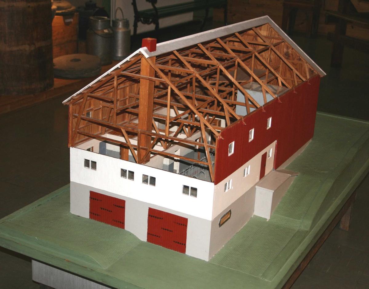 Modell av Lundfjøset  Tre, detaljer av ståltråd.  Grønnmalt plattform med en avtrapning. I den høyeste halvdel har gavlen to gråmalte kjørebroer, i den lavere halvdel 2 doble kjøreporter. Over underkjeller hvitmalt mur med fjøsvinduer, øvre del stående panel, rødmalt. 6 vinduer på den ene side i den panelte del, 3 på den andre. Den ene halvdel av taket dekket, den annen åpen.  Tilstand: den ene side sterkt falmet i det røde. Små detaljer som rekkverk etc. er løst, satt i stand på museet.