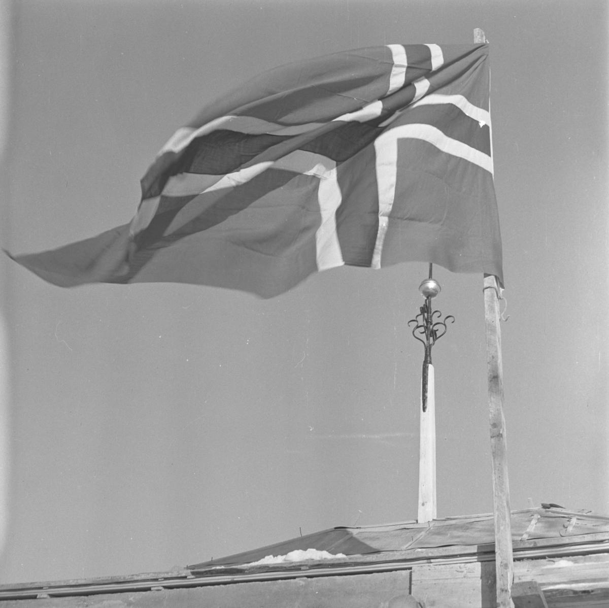 Aust-Agder-Museets første byggetrinn  på Langsæ.  Kranselag. Flagget vaiet og i bakgrunnen sees et spir med beslag av smijern.