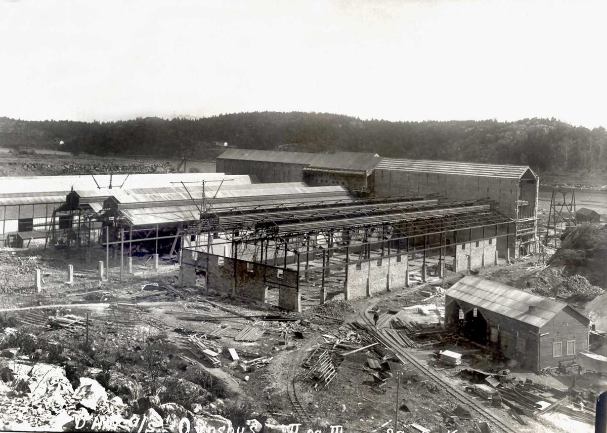 """""""20/11-1915"""" Nitriden. Bygging av Ovnshus II og III, sett fra høydebassenget. Omformerstasjonen utbygd i full lengde. Smie til høyre. Tromøysund og Tromøy i bakgrunnen. Skinneganger for interntransport med traller."""