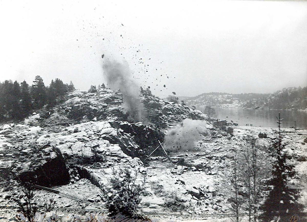 """""""1913"""" Nitriden. """"Nisser og dverge, bygger i berget"""". Utsprengning av fabrikktomten. Tomøysund og Tromøy til høyre."""
