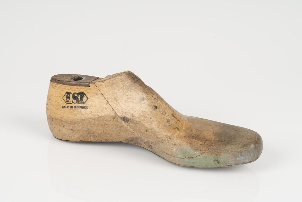 En tremodell i to deler; lest og opplest/overlest (kile). Venstrefot i skostørrelse 39, og 8 cm i vidde. Såle i metall.