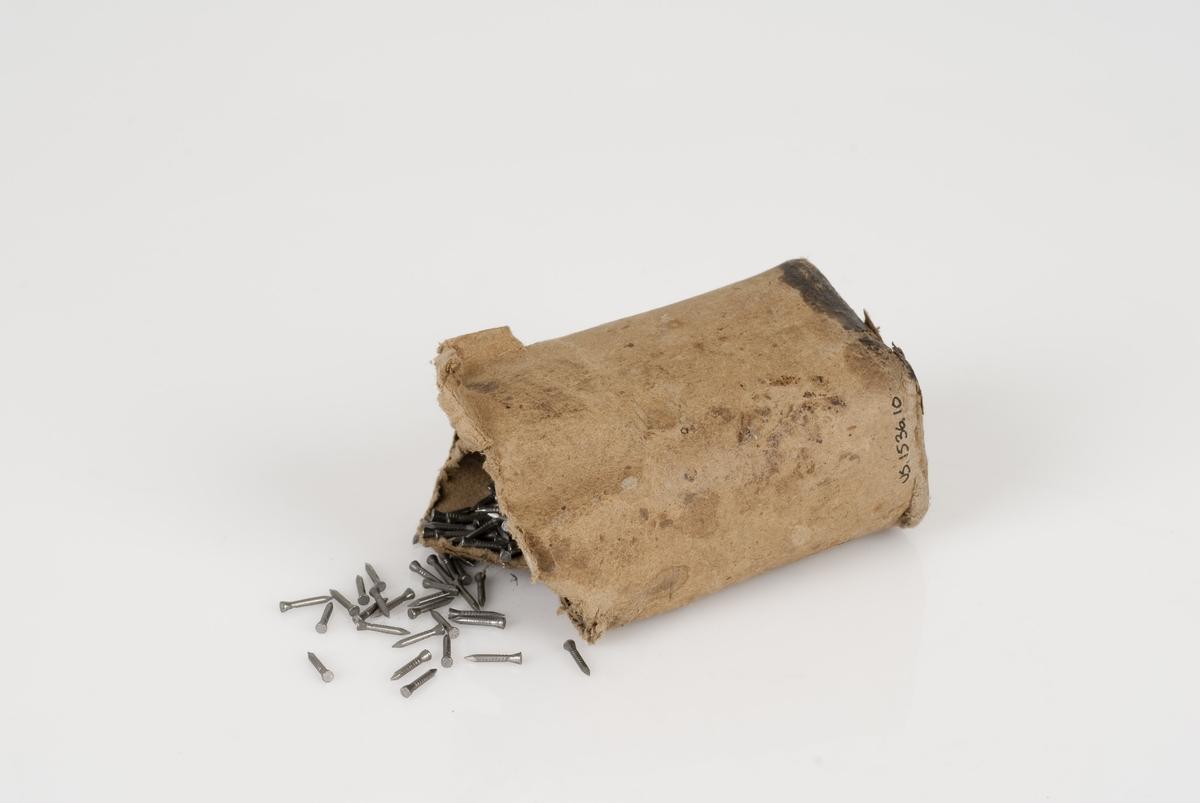 En eske som inneholder spiker av stål. Esken er rund.