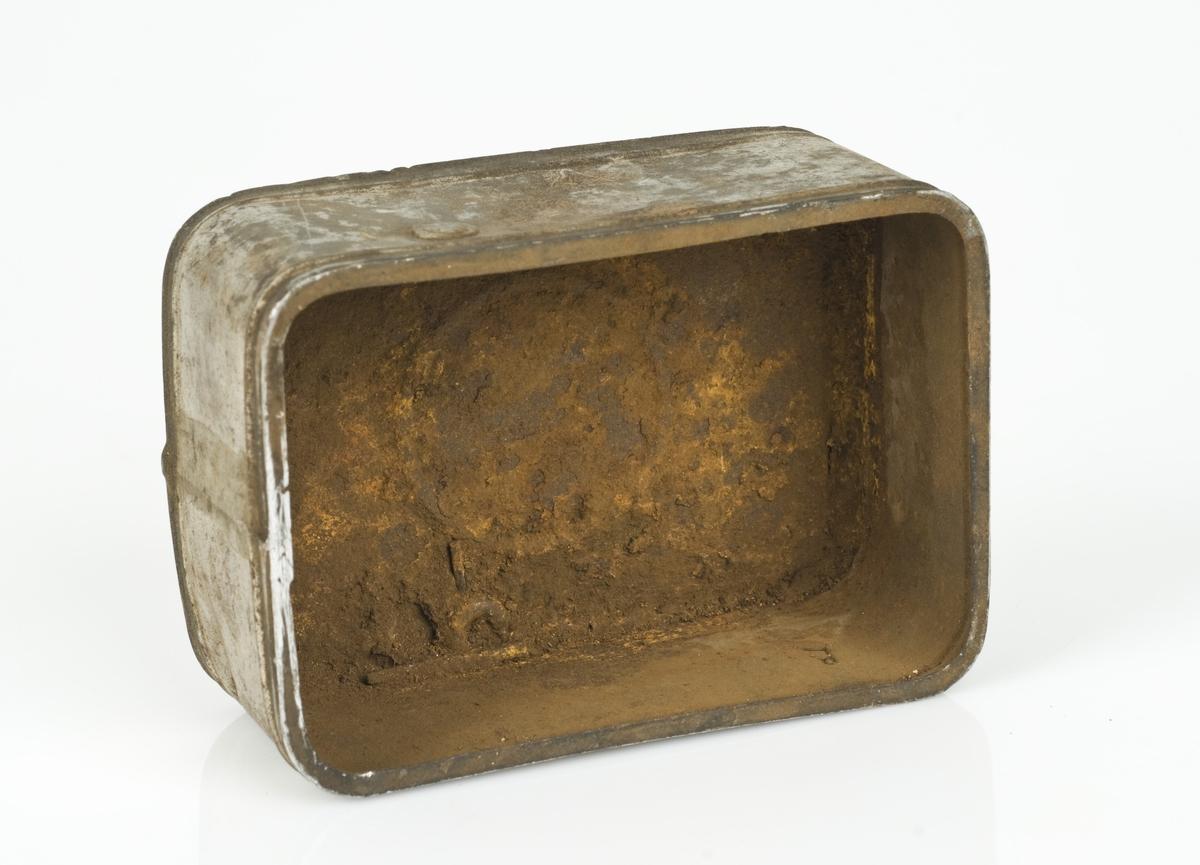 Rektangulær metallboks uten lokk. Boksen er tom.