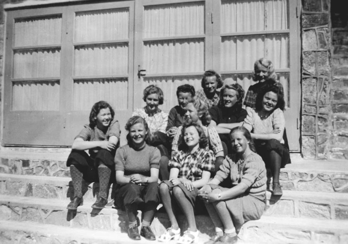 Elleve unge kvinner på en trapp.