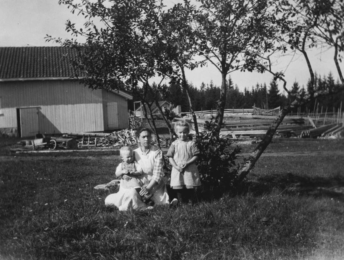 Kvinne med to barn i gresset.